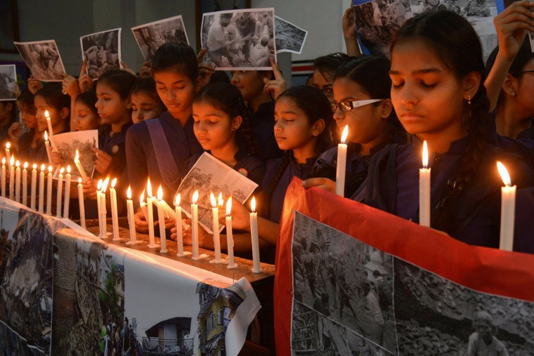 "Indian schoolgirls offer prayers for the victims of an earthquake in Nepal at a school in Amritsar on April 27, 2015. Nepalis started fleeing their devastated capital on April 27 after an earthquake killed more than 3,800 people and toppled entire streets, as the United Nations prepared a ""massive"" aid operation. (AFP Photo/P /narinder )"