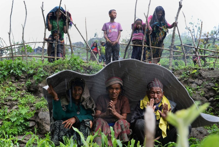 Nepalese villagers shelter from rain during relief operations following an earthquake at Lapu in Gorkha on Tuesday. Rescuers in Nepal battled to reach remote communities devastated by a huge earthquake that has killed at least 4,349 people, as the impoverished country's leader said relief workers had still not reached many of the worst-hit areas. (SAJJAD HUSSAIN/AFP/Getty Images)