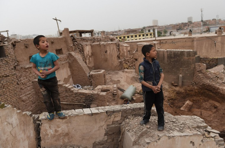 This photo taken on Sunday shows Uighur boys playing on the remains of houses in the old city in Kashgar, in China's western Xinjiang region. (GREG BAKER/AFP/Getty Images)
