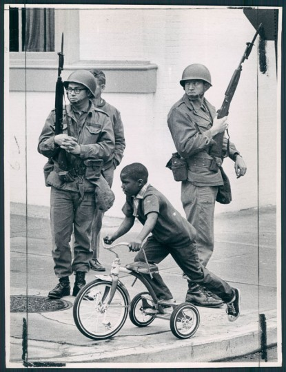April 9, 1968 - OBLIVIOUS -- Under the watchful eye of troops, this young man pedaled his tricycle at Twenty-fifth and Guilford. Photo by Paul Hutchins