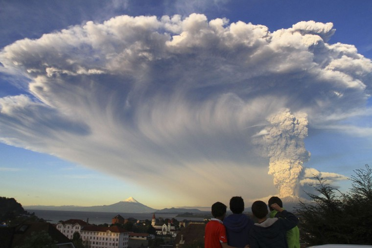 Children watch the Calbuco volcano erupt, from Puerto Varas, Chile, Wednesday, April 22, 2015. The volcano erupted billowing a huge ash cloud over a sparsely populated, mountainous area in southern Chile. Authorities ordered the evacuation of the inhabitants of the nearby town of Ensenada, along with residents of two smaller communities. (AP Photo/Carlos F. Gutierrez)