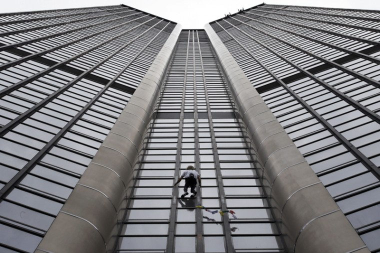 Alain Robert, also known as the French Spiderman, climbs the Montparnasse tower a 689-foot office skyscraper located in the Montparnasse area of Paris on Tuesday. Robert decided to climb in solidarity with the victims of Saturday's earthquake in Nepal. (Christophe Ena/AP)