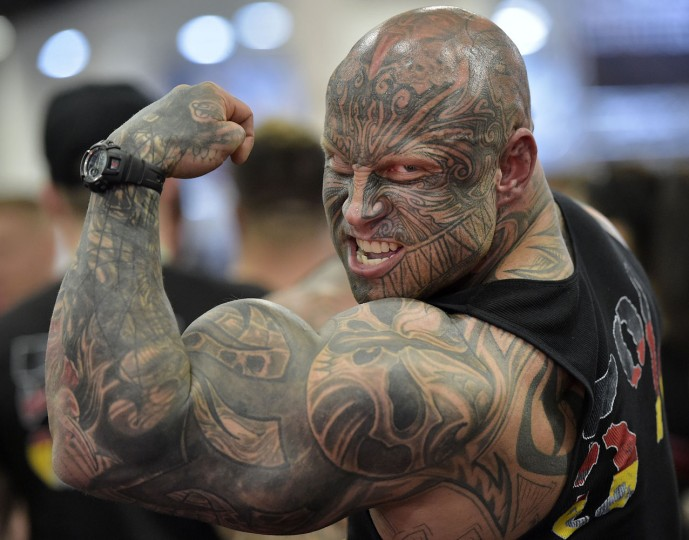 Bodybuilder Jens Dalsgaard from Denmark shows his muscles to visitors at the FIBO Power, a bodybuilding fair in Cologne, Germany, Thursday, April 9, 2015. (AP Photo/Martin Meissner)