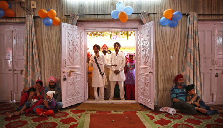 Indian Sikhs wait to offer prayers at a Sikh temple on Baisakhi, in New Delhi, India, on Tuesday. Baisakhi, the harvest festival celebrated in the Punjab region, coincides with other festivals celebrated on the first day of Indian calendar month Vaisakh. The festival has special significance for Sikhs since it marks the day in 1699 when their tenth Guru Gobind Singh organized the order of the Khalsa, a collective body of initiated Sikhs. (Manish Swarup/AP)