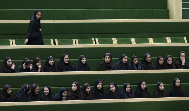 Iranian school girls follow the debates of the parliament in Tehran on Tuesday. (Vahid Salemi/AP)