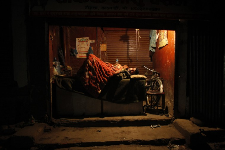 A man sleeps in his store with the shutters open in Kathmandu, Nepal, on Tuesday. Across central Nepal, including in Kathmandu, the capital, hundreds of thousands of people are still living in the open without clean water or sanitation after Saturday''s massive earthquake, one of the worst to hit the South Asian nation in more than 80 years. (Niranjan Shrestha/AP)