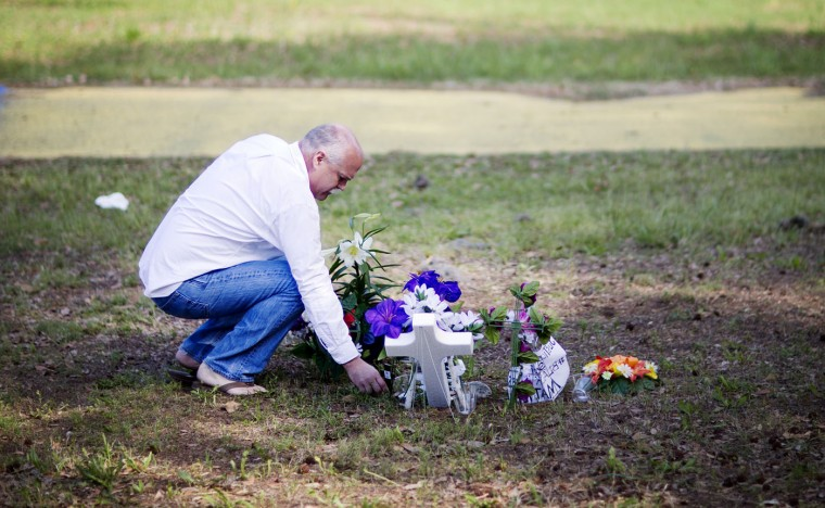 """Jeffrey Spell, of Charleston, S.C., places flowers at the scene where Walter Scott was killed by a North Charleston police officer Saturday, after a traffic stop in North Charleston, S.C., Thursday, April 9, 2015. """"I've worked in North Charleston for many years and I'm troubled by the whole thing. I thought it would be respectable,"""" said Spell about why he brought the flowers. """"Nationwide, the cops are killing people. There has to be other ways of making arrests,"""" Spell said. The officer, Michael Thomas Slager, has been fired and charged with murder. (AP Photo/David Goldman)"""