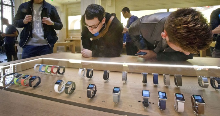 Customers examine the new Apple watches presented at the Paris Opera Apple store Friday April 10, 2015. From Beijing to Paris and San Francisco, the Apple Watch made its world debut Friday. Customers were invited to try them on in stores and order them online. (Michel Euler/AP photo)