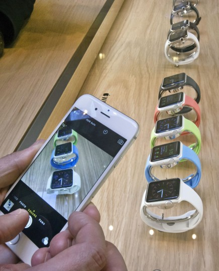 A customer takes snapshots of new Apple watches presented at the Paris Opera Apple store Friday April 10, 2015. From Beijing to Paris and San Francisco, the Apple Watch made its world debut Friday, with customers invited to try them on in stores and order them online. (Michel Euler/AP photo)