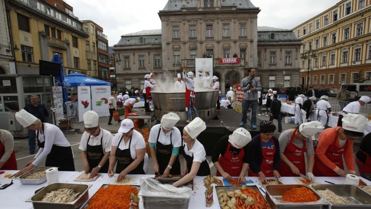 Bosnian cooks and volunteers prepare a chicken stew in Sarajevo, on Friday April 17, 2015. Bosnian chefs hope they have broken a Guinness record for the biggest chicken stew in the world, cooking up a meal for 14,000 people. The pot was set up in the center of Sarajevo and once the cooking was over the food was served to hundreds of people who gathered to watch the spectacle.  || CREDIT: AMEL EMRIC - AP PHOTO