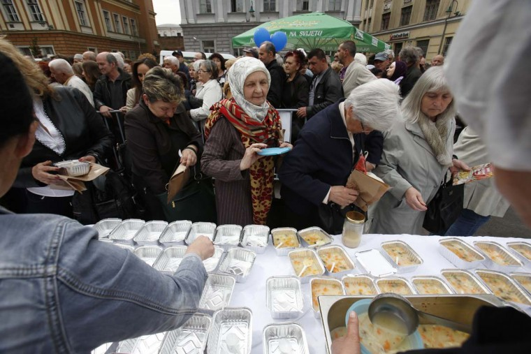 Bosnian people gather to taste chicken stew after cooks and volunteers prepared the stew in Sarajevo, on Friday April 17, 2015. Bosnian chefs hope they have broken a Guinness record for the biggest chicken stew in the world, cooking up a meal for 14,000 people. The pot was set up in the center of Sarajevo and once the cooking was over the food was served to hundreds of people who gathered to watch the spectacle.  || CREDIT: AMEL EMRIC - AP PHOTO