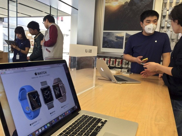 Staff members attend to customers near a display about Apple Watch at an Apple retail store in Beijing, Friday, April 10, 2015. (Ng Han Guan/AP photo)