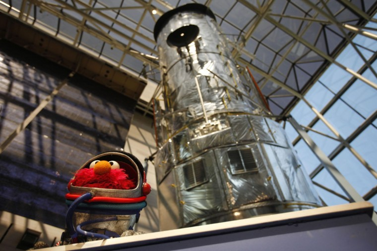 Elmo makes an appearance in front of a model of the Hubble telescope during an announcement about a new planetarium show for kids at the National Air and Space Museum. (2009 AP Photo/Jacquelyn Martin)