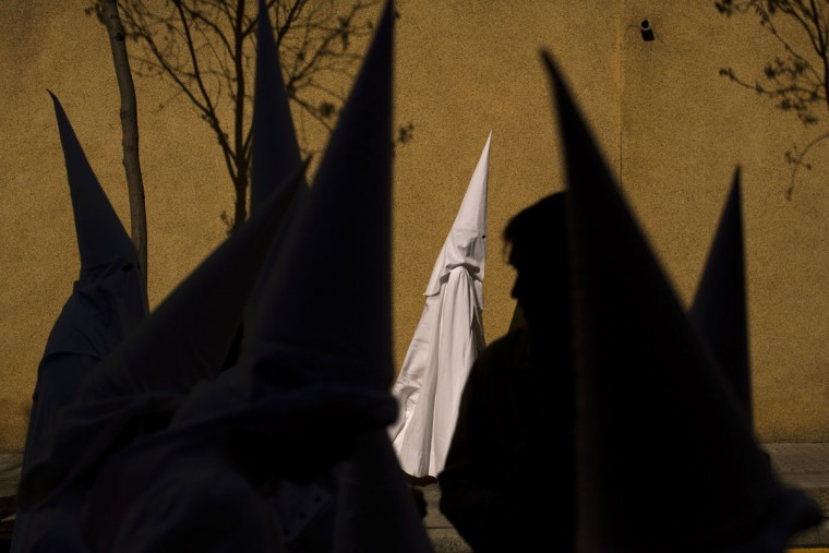 Hooded penitents from the La Paz brotherhood walk to the church to take part in a procession in Seville, Spain. Hundreds of processions take place throughout Spain during the Easter Holy Week. (AP Photo/Emilio Morenatti, FILE)