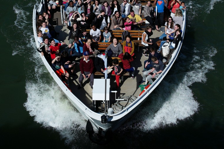 Tourists ride in a tour boat in Paris on Tuesday. (Thibault Camus/AP)