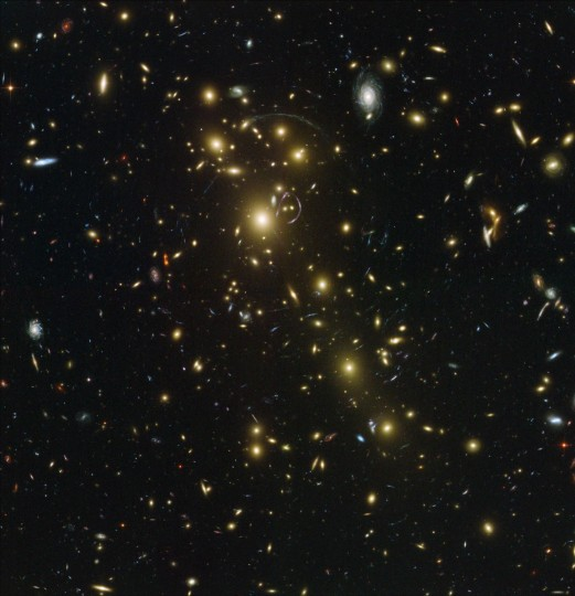 This Hubble image shows Abell 1703 which is composed of over 100 different galaxies whose collective mass acts as a gravitational lens. The massive galaxy cluster in the foreground (yellow mostly elliptical galaxies scattered across the image) bends the light rays of galaxies behind it in a way that can stretch their images into multiple arcs. (NASA/ESA, and Johan Richard via AP)