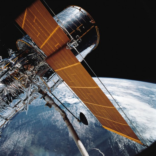 Most of the Hubble Space Telescope can be seen as it is suspended in space by Discovery's Remote Manipulator System following the deployment of part of its solar panels and antennae. (1990 NASA photo via AP) ORG XMIT: NY122