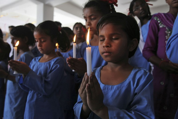 School children hold candles and offer prayers for victims of Nepal's earthquake, at a temple in Gorkha Nagar in Jammu, India, Monday, April 27, 2015. A strong magnitude earthquake shook Nepal's capital and the densely populated Kathmandu valley on Saturday devastating the region and leaving tens of thousands shell-shocked and sleeping in streets. (AP Photo/Channi Anand)