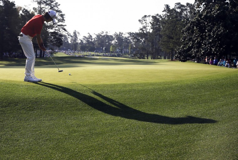 Kevin Na putts on the first green during the first round of the Masters golf tournament Thursday, April 9, 2015, in Augusta, Ga. (AP Photo/Darron Cummings)