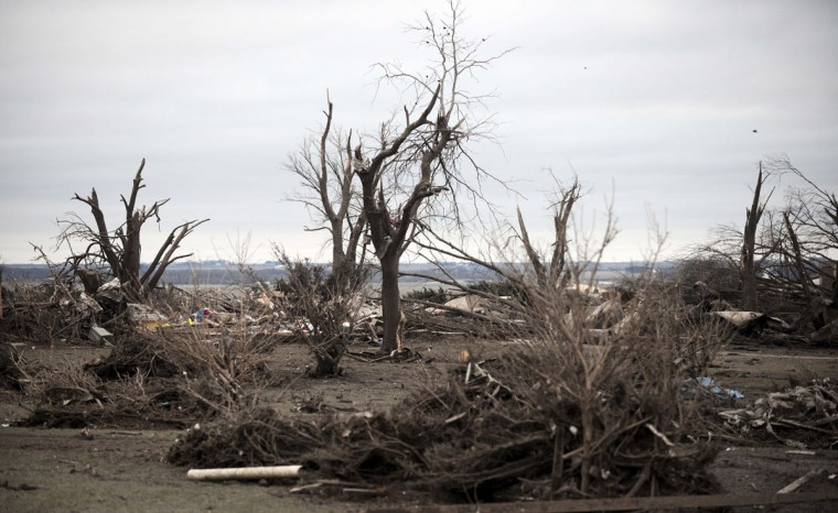 Torn-up trees and debris cover the ground in Rochelle, Ill., Friday morning, April 10, 2015, after a tornado blew through the area Thursday evening. The National Weather Service says at least two tornadoes churned through six north-central Illinois counties. One person was killed in the small town of Fairdale, Ill. (AP Photo/Daily Herald, Paul Michna)