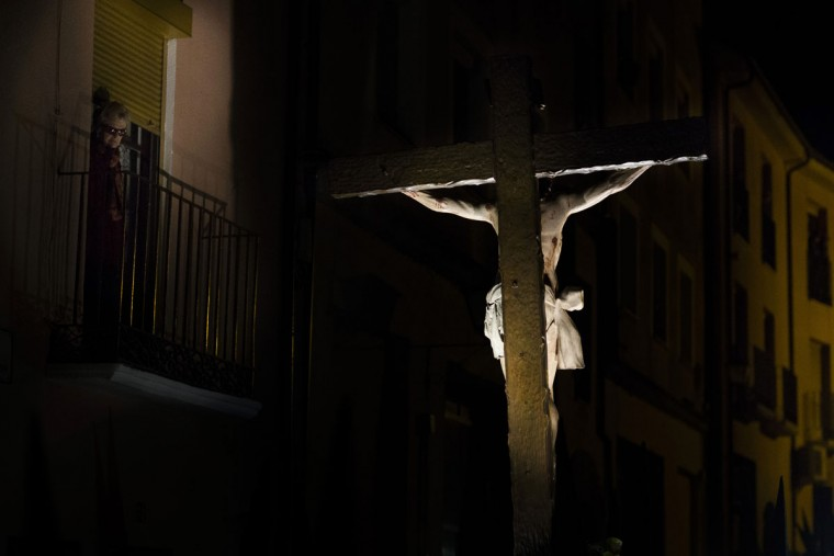 "A woman watches as penitents from ""Las Siete Palabras (Seven words)"" brotherhood carry an image of Jesus Christ during a procession in Zamora, Spain, on the early hours of Wednesday, April 1, 2015. Hundreds of processions take place throughout Spain during the Easter Holy Week. (AP Photo/Andres Kudacki)"