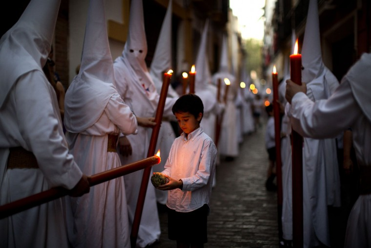 "A boy collects wax from a penitent large candle during the procession of ""La Candelaria"" brotherhood in Seville, Spain, Tuesday, March 31, 2015. Hundreds of processions take place throughout Spain during the Easter Holy Week. (AP Photo/Emilio Morenatti)"