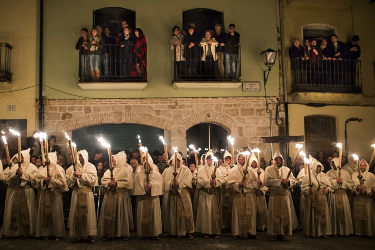 People watch as penitents from 'Cristo de la Buena Muerte' or 'Good Dead Christ' brotherhood take part in a procession in Zamora, Spain, early Tuesday, March 31, 2015. Hundreds of processions take place throughout Spain during the Easter Holy Week. (AP Photo/Andres Kudacki)