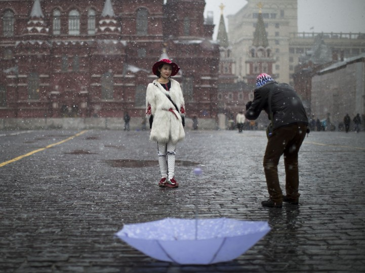 Chinese tourists take photographs at Red Square during a snowfall in Moscow, Russia, Friday, April 3, 2015. (AP Photo/Alexander Zemlianichenko)