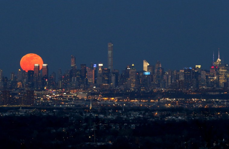 A full moon is seen as it rises over the New York City skyline seen from West Orange, N.J., Saturday, April 4, 2015. (AP Photo/Julio Cortez)