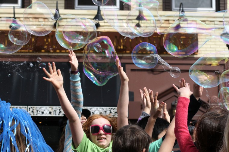 Kids try to pop bubbles before the start of Festifools in downtown Ann Arbor, Mich. (Patrick Record/The Ann Arbor News via AP)