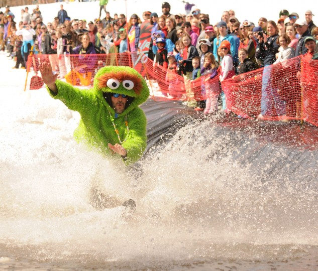 Dressed as Oscar the Grouch, Christo Moeller of New York City makes a splash while attempting to ski across a man-made pond at the Whiteface Mountain Ski Center in Wilmington, N.Y. during the resort's annual Pond Skimming contest on Sunday, April 12, 2015. (Lou Reuter/Adirondack Daily Enterprise via AP)