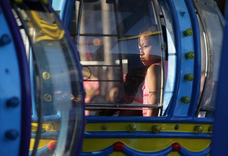 A Filipino girl stands inside a Ferris Wheel in suburban Makati, south of Manila, Philippines on Sunday, April 12, 2015. (AP Photo/Aaron Favila)