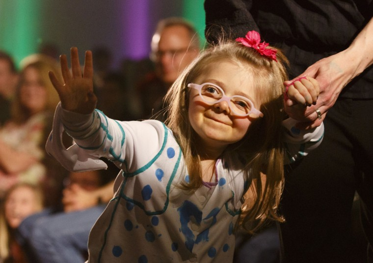 Josie Black, 4, waves to the audience from the runway during the DisArt Fashion Show at the Woodbridge N. Ferris Building in Grand Rapids, Mich., Friday, April 17, 2015. The third group featured clothing for children with disabilities that is convenient to dress and undress designed by Kendall's fashion studies that partnered with Spectrum Health. (Hugh Carey/The Grand Rapids Press via AP)