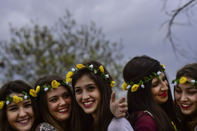 Young women wearing flowers in their hair smile toward the photographer during a spring day, in Pamplona, northern Spain, Friday April 17, 2015. (AP Photo/Alvaro Barrientos)