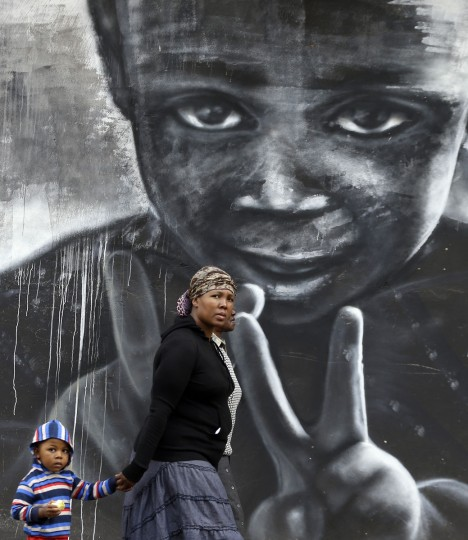 A woman and child walk past a mural in downtown Johannesburg, South Africa, Sunday, April 19, 2015. (AP Photo/Themba Hadebe)