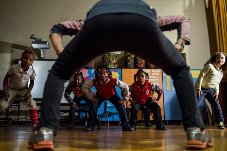 First-grade twins Zamaria and Zamarea Ward, both 6, follow along with CrimFit coach Amelia Schmid, 23, who leads a morning fitness group of first and second grade students on Wednesday, April 22, 2015 at Brownell STEM Academy in Flint, Mich. Community education will expand to three more buildings within the Flint School District beginning next fall. The Crim Fitness Foundation is the lead agency, with about 20 other community partners that are involved. The community education model was created in Flint, but was phased out in the 1980s because of budget constraints. (Jake May/The Flint Journal-MLive.com via AP) LOCAL TELEVISION OUT; LOCAL INTERNET OUT (REV-SHARE) (ONLN OUT; IONLN OUT - MBI)