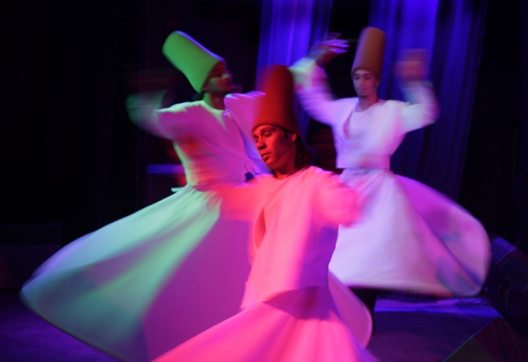 """Egyptian whirling dervishes dance in traditional costumes as they perform Sufi dance known as """"whirling dervish."""" in Cairo, Egypt, Thursday, April 23, 2015. Whirling dervishes of al-Tannura entertain visitors with their colorful and artistic spinning dance. (AP Photo/Amr Nabil)"""