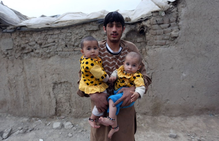 An Afghan man poses for a photograph as he carries his twin nieces, on the outskirts of Kabul, Afghanistan, Sunday, April 26, 2015. (AP Photo/Rahmat Gul)