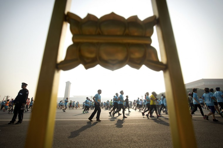 Runners in a 10-kilometer (6.25 mile) road race pass along a road next to Tiananmen Square on a hazy day in Beijing, Sunday, April 26, 2015. More than 20,000 runners were expected to participate in the annual Beijing Run on Sunday despite unhealthy levels of air quality, according to official Chinese government pollution readings. (AP Photo/Mark Schiefelbein)