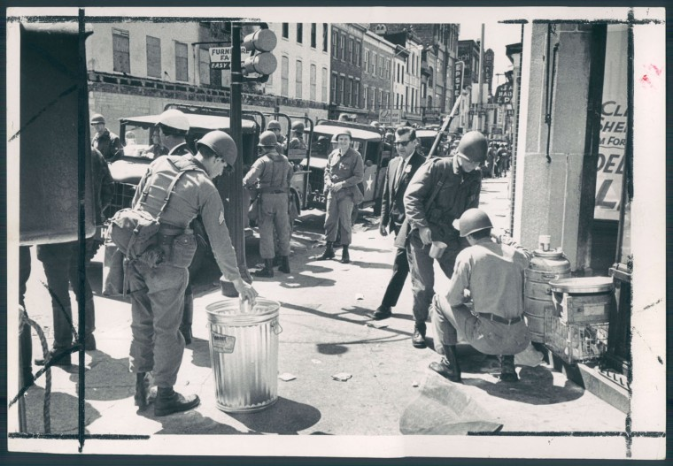 Tired troopers relax with coffee at Gay and Aisquith streets during 1968 riots as burning and looting declines.