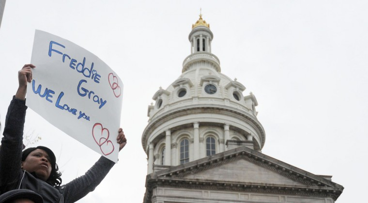 """Tynu Wells, 38, E. Baltimore, holds up a sign that reads """"Freddie Gray We Love You"""" outside City Hall. March from Mount Street and Presbury Streets in Sandtown/WInchester, where Freddie Gray was arrested, to CIty Hall to protest the death of Gray in police custody. (Kim Hairston/The Baltimore Sun)"""