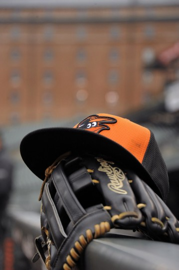 A cap and glove owned by Baltimore Orioles designated hitter Delmon Young rests at the dugout during the Orioles' home opener at Oriole Park at Camden Yards. (Karl Merton Ferron/Baltimore Sun)