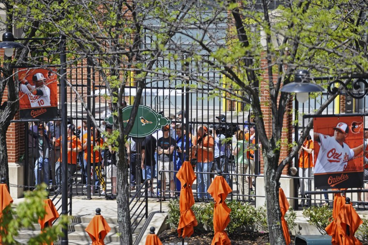 Orioles fans, who were locked out of the game, watched the first inning of the game from outside the flag court gate at Camden Yards. Fans were not allow into the game because of safety concerns. The Orioles plays the Chicago White Sox to an empty Oriole Park at Camden Yards on Wednesday. The first two games of the series were cancelled due to the wide spread riots and looting on Monday in Baltimore resulting from protest over the death of Freddie Gray. (Kenneth K. Lam/Baltimore Sun)