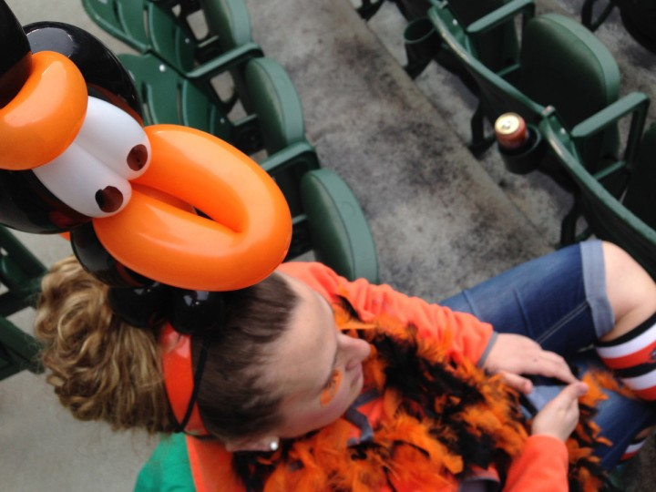"""Jennifer George, Cleveland, grew up a fan of Cal Ripken, as she has family in Aberdeen.""""I love the Orioles,"""" she said.  """"I love opening day, and wanted to have my first opening day experience."""" She got the balloon hat at Pickles Pub. (Christopher T. Assaf/Baltimore Sun)"""