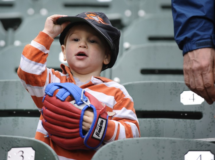 Andrian Webbert, 3, of Baltimore, tries to catch a fly ball from right field during batting practice. Webbert is attending his second opening day games with his father and grandfather. (Kenneth K. Lam/Baltimore Sun)