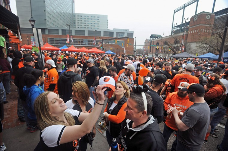 Patricia Horney, left, of Cockeysville, compares her Orioles cap to her friend David Dvorak's, of Joppatowne, O's head gear as they wait across the street from Oriole Park on Opening Day. (Kenneth K. Lam/Baltimore Sun)