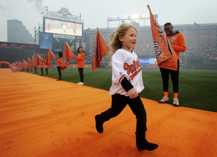 """Ellie Miller, 6, of Havre de Grace, runs onto the field at Camden Yards as the representative of the fans, the """"10th Man.""""  (Kenneth K. Lam/Baltimore Sun)"""