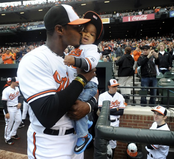 Orioles centerfielder Adam Jones kisses his son, Zaniyah, before taking the field against the Blue Jays in the home opener. The Baltimore Orioles play the Toronto Blue Jays in the opening home game of the 2015 season.   (Kenneth K. Lam/Baltimore Sun)