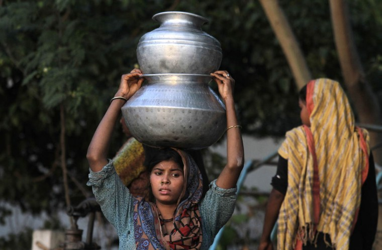 A Pakistani girl carries clean water to her home in Lahore's slums in Pakistan. There is a scarcity of fresh drinking water in Pakistan among a population of around 180 million. (K.M. Chaudary/AP photo)
