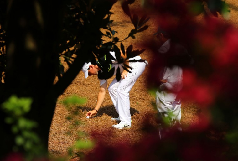 Seen through the foliage, Rory McIlroy has to take a drop off the #2 fairway during the first round at the Masters Golf Tournament, Thursday, April 9, 2015 in Augusta, Ga. (Curtis Compton/Atlanta Journal-Constitution/TNS)